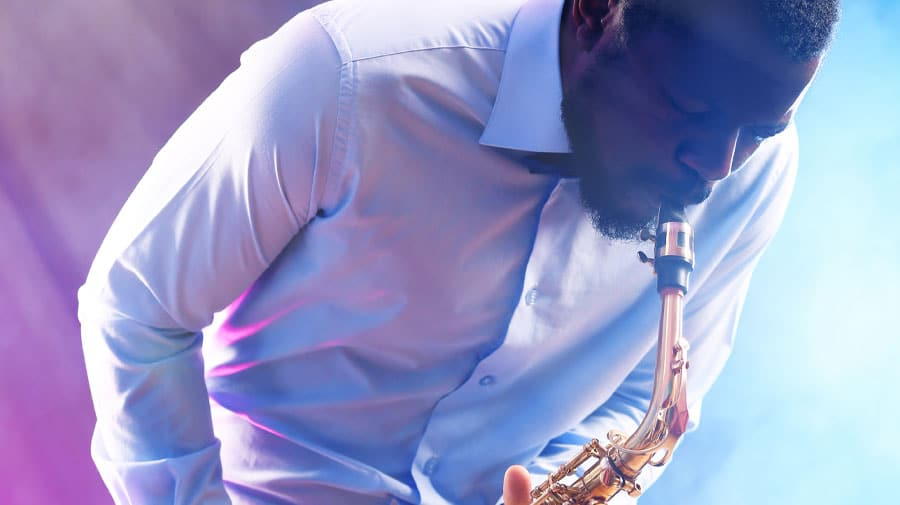 african american jazz musician playing saxophone against colorful smoky - The Capital Hotels & Apartments 5